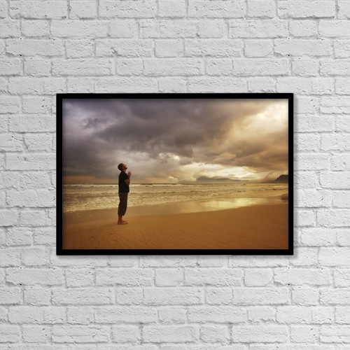 """Printscapes Wall Art: 18"""" x 12"""" Canvas Print With Black Frame - Man Praying On A Beach by Kristy-Anne Glubish"""