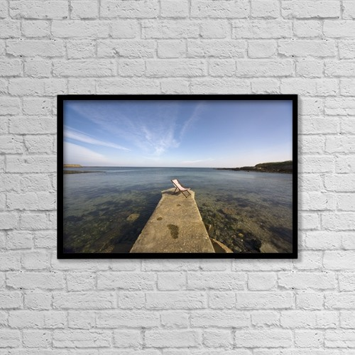 "Printscapes Wall Art: 18"" x 12"" Canvas Print With Black Frame - Lonely Deckchair At The Edge Of Pier by John Short"