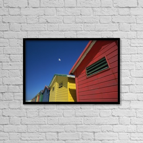 "Printscapes Wall Art: 18"" x 12"" Canvas Print With Black Frame - Seagull Flying Over Colorful Beach Huts by Ian Cumming"