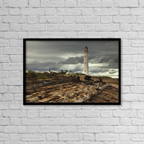 "Printscapes Wall Art: 18"" x 12"" Canvas Print With Black Frame - A Lighthouse And Piles Of Logs On The Shore by John Short"