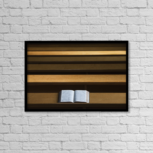 """Printscapes Wall Art: 18"""" x 12"""" Canvas Print With Black Frame - A bible open on a wooden bench by John Short"""